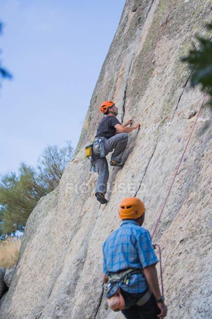 Adventurers climbing mountain, wearing safety harness against picturesque landscape - foto de stock