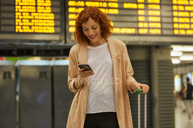 Happy red headed young woman with suitcase smiling and chatting on mobile phone at station — Stock Photo