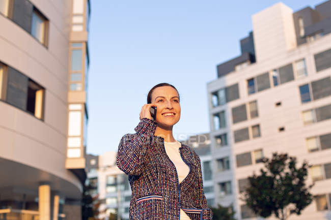 Cheerful female entrepreneur smiling and looking away while talking on smartphone — стокове фото