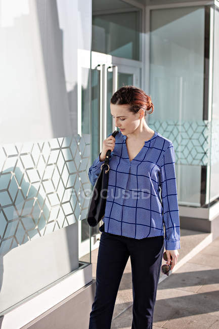 Businesswoman in elegant outfit looking down and standing on pavement outside building with glass walls — Stock Photo