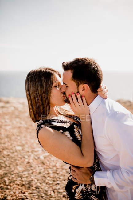 Літом я бачу, як пристрасна жінка і чоловік ніжно цілуються на природі. — стокове фото