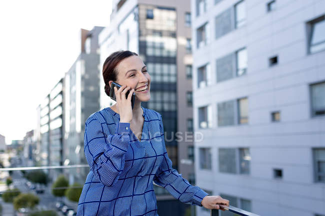 Beautiful businesswoman in blue checkered shirt frowning and looking away while standing on balcony — стокове фото