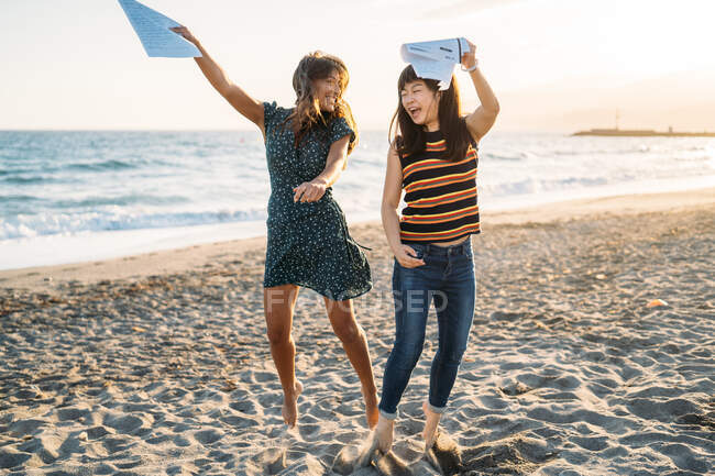 Two beautiful women dancing on the beach, a girl with brown hair and a girl with Asian features — Stock Photo