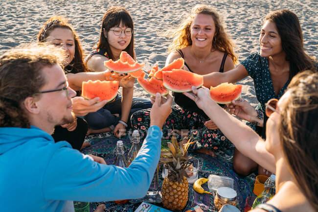 Группа друзей на пляже собирает свои куски арбуза — стоковое фото