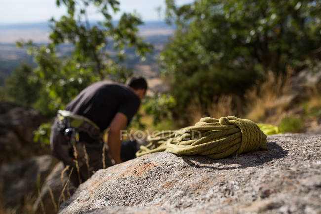 Rope on rock with defocused climber on the background preparing his equipment to start climbing - foto de stock