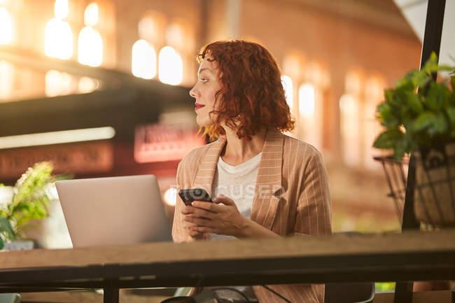 Joyeux jeune femme travaillant sur ordinateur portable dans le café et téléphone de navigation — Photo de stock