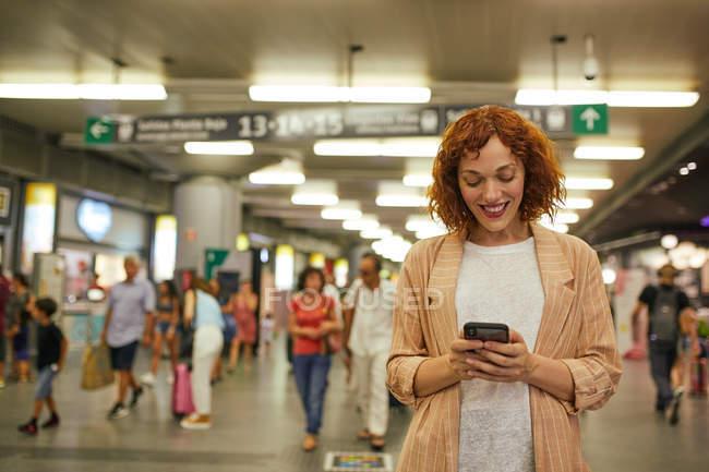 Jovem ruiva usando smartphone na estação — Fotografia de Stock