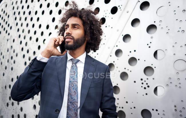 Homme d'affaires afro-américain présentable lors d'une conversation téléphonique — Photo de stock