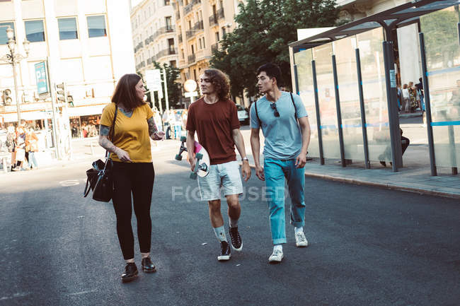 Happy carefree people in casual clothes embracing and strolling together along urban street — Stock Photo