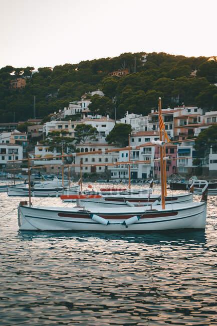Yate blanco flotante en aguas tranquilas de la bahía contra la pequeña ciudad en la costa en el crepúsculo - foto de stock