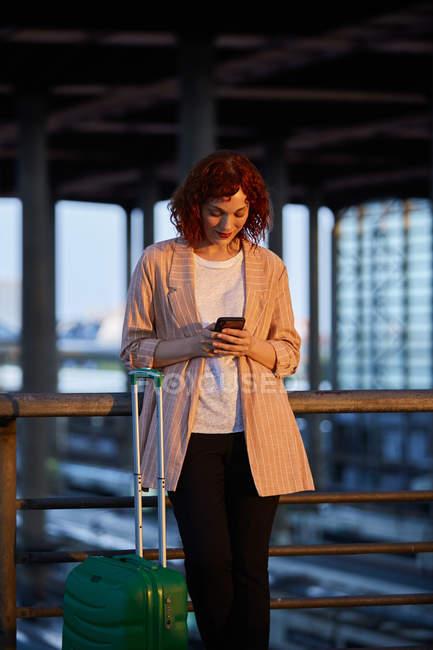 Улыбающаяся молодая женщина, просматривающая телефон на станции — стоковое фото