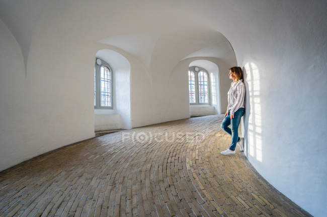 Side view of calm woman in jeans leaning on white wall at minimalistic hall with arched windows — Stock Photo