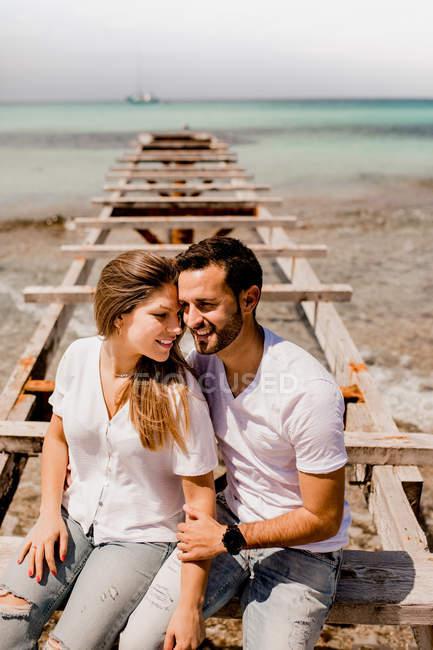 Encantados amantes sentados en el muelle destruido en la orilla del mar - foto de stock
