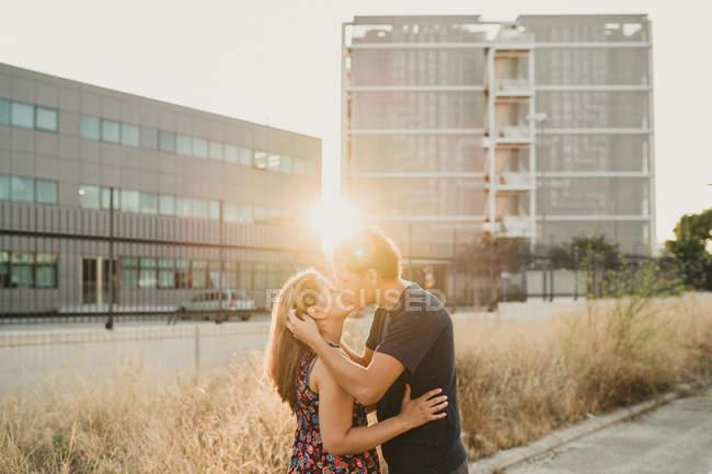 Vue latérale d'un couple romantique embrassant et embrassant sur la route le long d'un immeuble urbain en plein soleil — Photo de stock