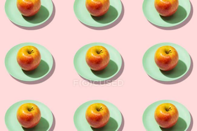 Frischer Apfel im Teller auf rosa Hintergrund. Lebendiges buntes Muster — Stockfoto