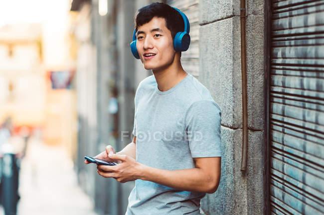 Gioioso casual asiatico uomo in cuffie utilizzando smartphone mentre in piedi sulla strada soleggiata della città — Foto stock