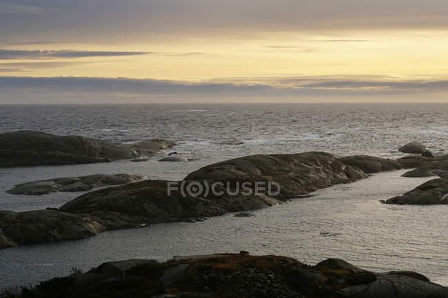 Glatte Felsbrocken an leerer Küste mit Meereswellen unter dunklem Abendhimmel in Norwegen — Stockfoto