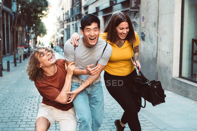 Улыбающиеся мультиэтнические люди в повседневной одежде, играющие во время прогулки по городской улице — стоковое фото