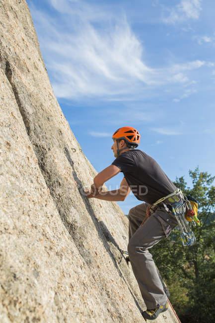 Homem escalando uma rocha na natureza com equipamento de escalada — Fotografia de Stock