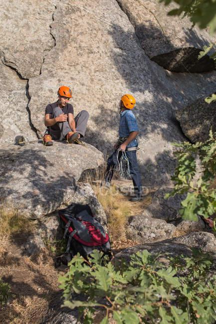 Escalador se está poniendo sus zapatos de escalador para empezar a escalar - foto de stock