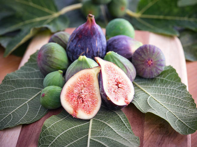 Chopped fig and figs over wooden table with green leaves — Stock Photo