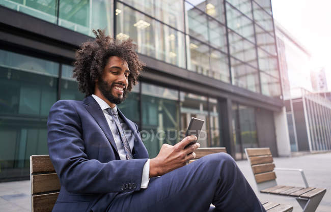 Joyful african american man in suit sitting outside and messaging — Stock Photo