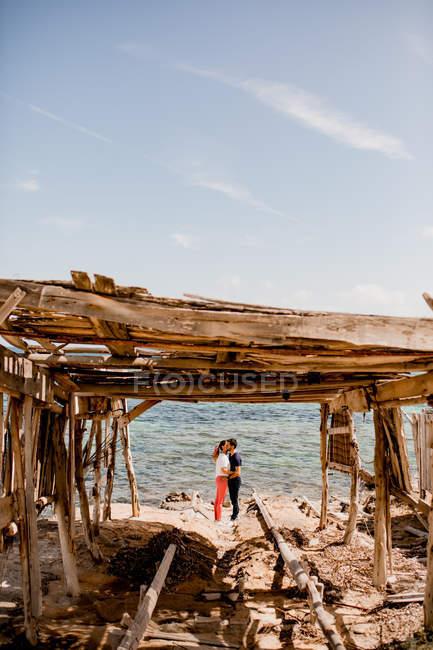 Gli amanti pacifici abbracciano in riva al mare — Foto stock
