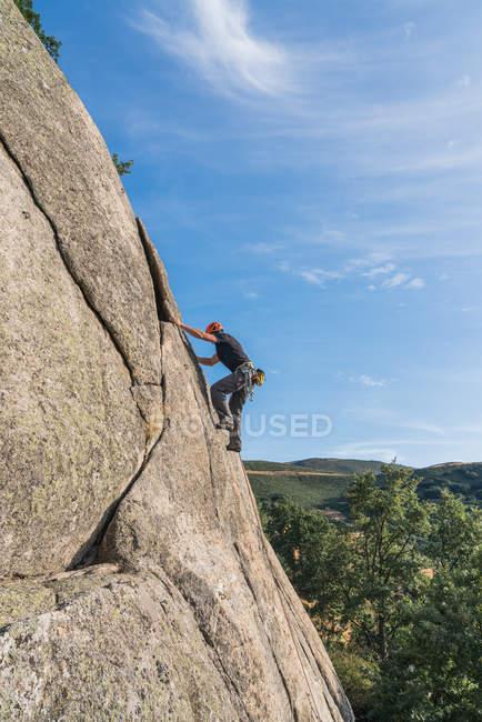 Знизу людина піднімається на скелі з альпіністським обладнанням. — стокове фото