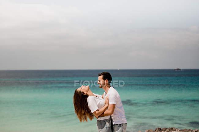 Gli amanti ridenti che si abbracciano sulla spiaggia — Foto stock