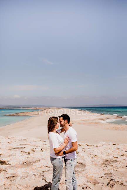 Seitenansicht des anhänglichen Mannes und der Frau in Freizeitkleidung, die im Sommer an der Küste kleben — Stockfoto
