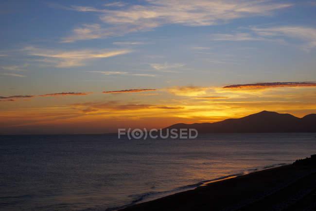 Pôr-do-sol brilhante acima da misteriosa paisagem de águas onduladas que lavam a costa rochosa em Lanzarote, Ilhas Canárias, Espanha — Fotografia de Stock