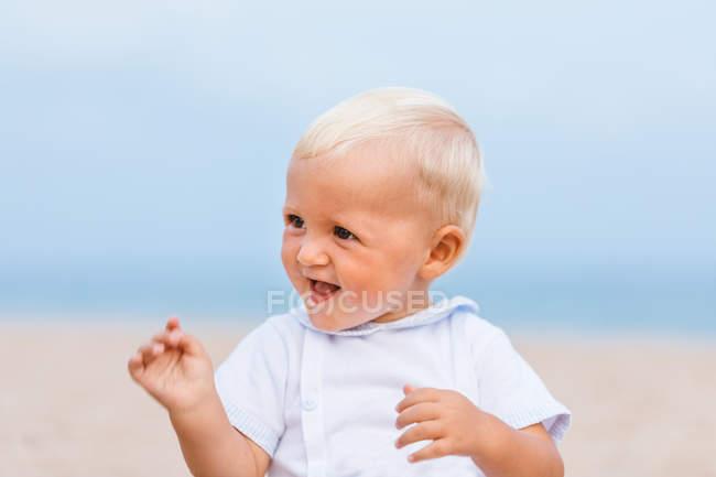 Retrato de un bebé rubio sonriendo en la playa - foto de stock