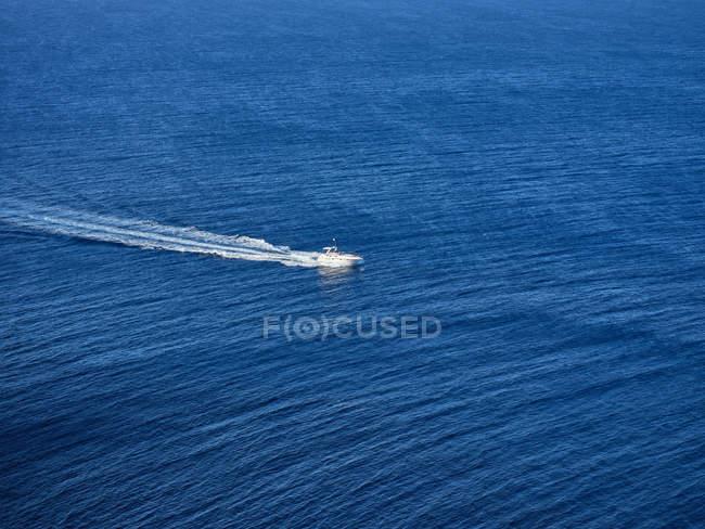 Du haut d'un yacht blanc flottant rapidement laissant une empreinte moussante à travers des eaux bleues sereines dans un océan sans fin — Photo de stock