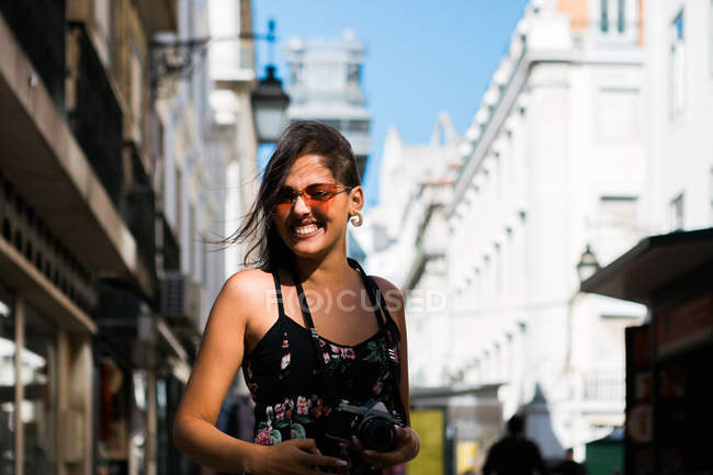 Playful woman in long dress holding a photo camera while walking along city summer street — Stock Photo