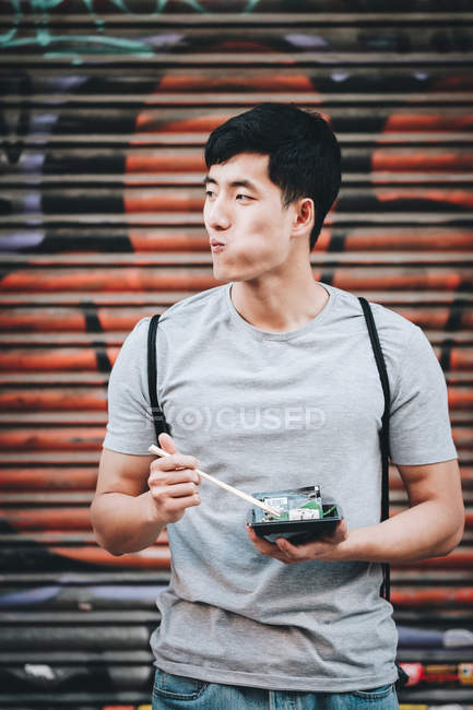Handsome asian man eating takeaway food while standing by food truck on the street — Stock Photo