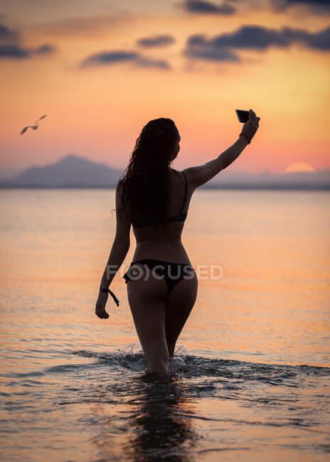 Seductive female taking selfie in water — Stock Photo