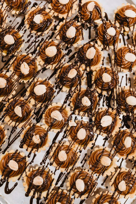 Closeup set of yummy pastry with sweet caramel cream and nuts arranged on parchment paper — Stock Photo