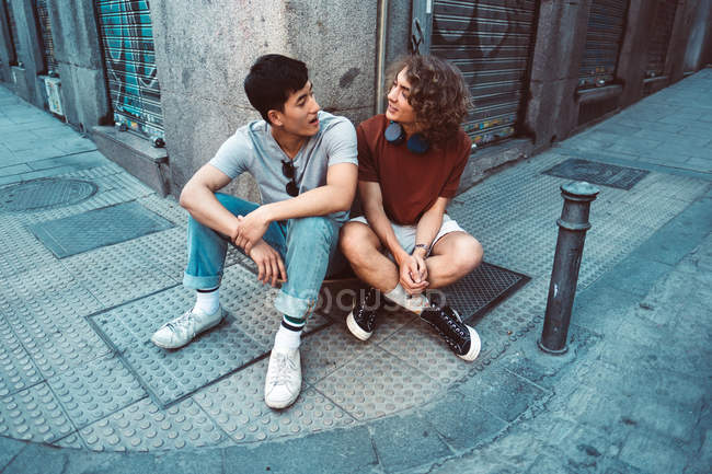 Cool modern multiethnic men in casual outfit having discussion while sitting on pavement by building corner together — Fotografia de Stock