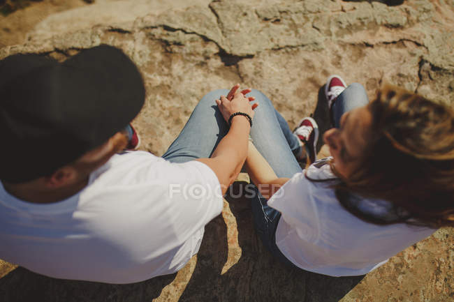 Happy couple sitting at mountain cliff — Stock Photo