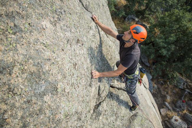 De cima homem escalando uma rocha na natureza com equipamento de escalada — Fotografia de Stock
