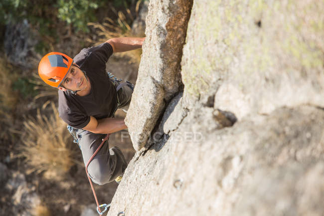 From above man climbing a rock in nature with climbing equipment — Stock Photo