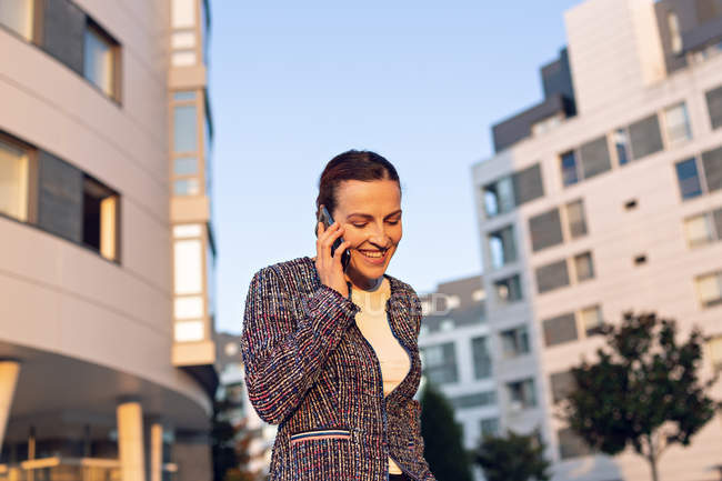 Cheerful female entrepreneur smiling and looking away while talking on smartphone and standing on street — стокове фото