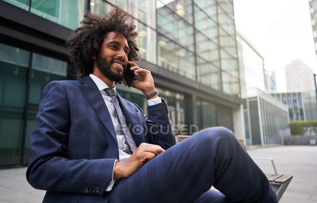 Joyful african american man in suit sitting outside and talking by phone — Stock Photo