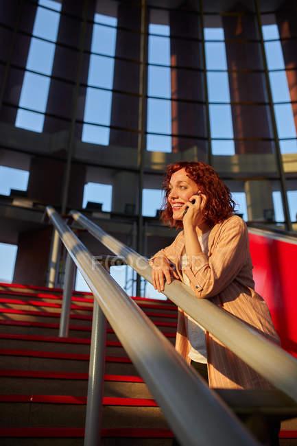 Beautiful young woman communicating via smartphone at station — Stock Photo