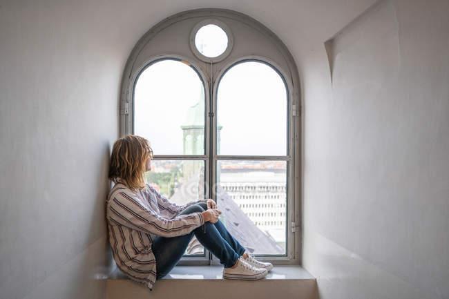 Seitenansicht einer träumenden modernen Frau, die auf einem Fensterbrett sitzt und aus einem gewölbten Fenster blickt — Stockfoto