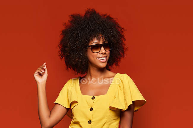 African American woman posing while smiling at camera on bright red background — Stock Photo