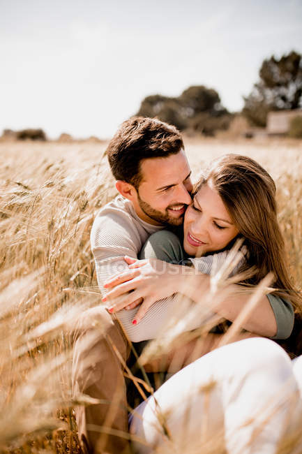 Sensual loving man and woman hugging on rye field in summer on blurred background — Stock Photo
