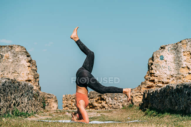 Flexible woman stretching and practicing yoga at sunny countryside — Stock Photo