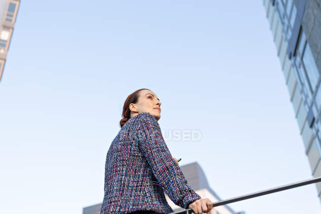 Low angle of serious female manager in elegant outfit leaning on railing and looking away on street — Photo de stock