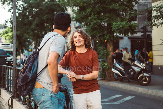 Carefree interested multiethnic men in casual clothes talking while standing city street — Fotografia de Stock